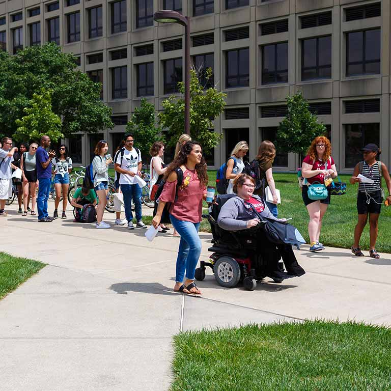 Students walk down a sidewalk on the IUPUI campus.