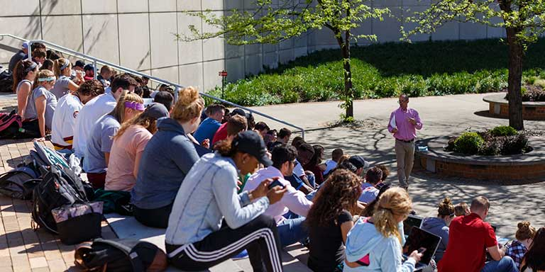 Students sitting on steps outdoors listen to a speaker who is standing under a tree.