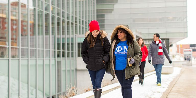 Students walk by the IUPUI Campus Center on a snowy day.
